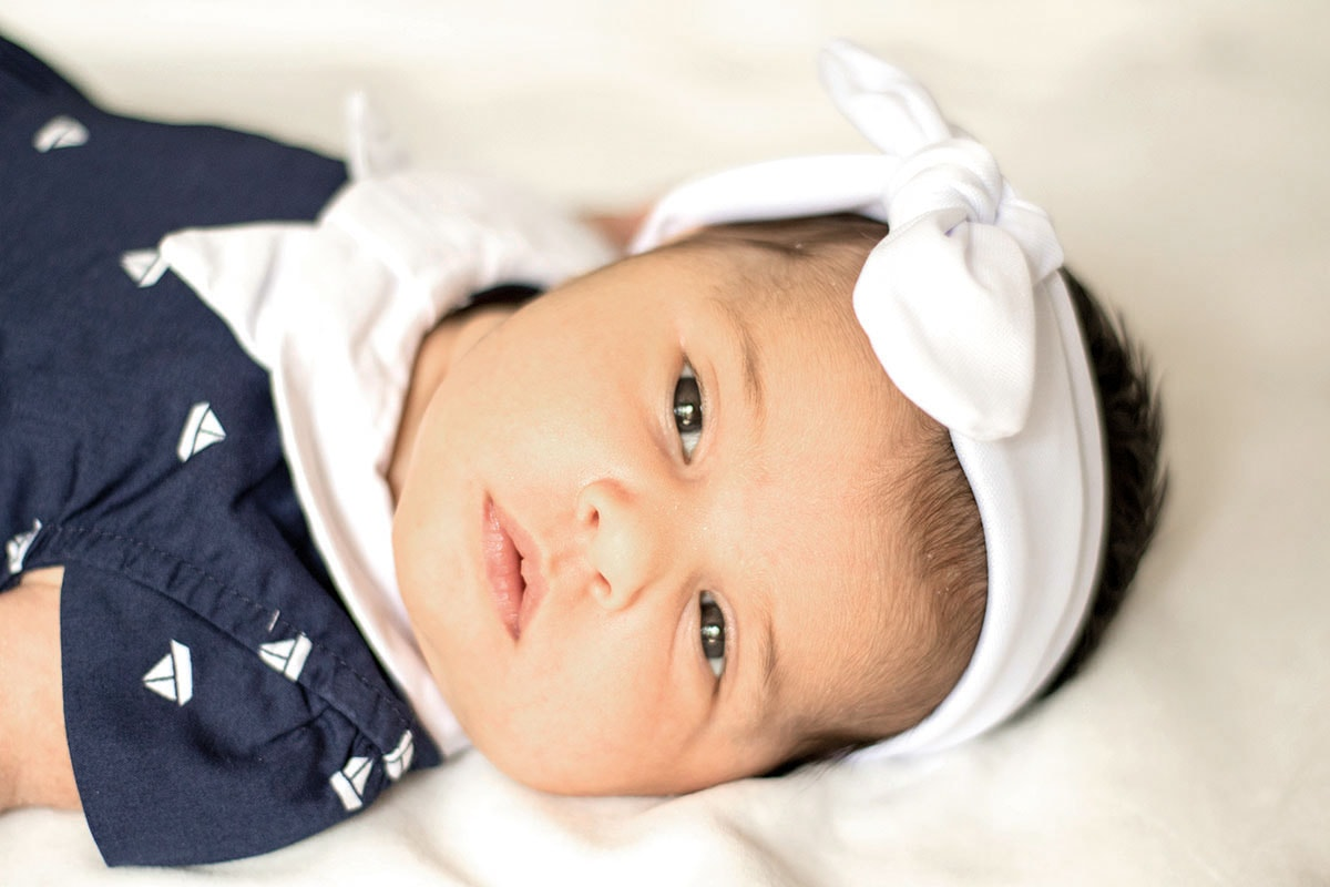 Fotografie. Babyfotos. Baby mit Seemannskleid mit weißer Schleife in den Haaren.