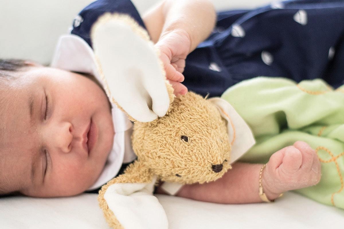 Fotografie. Babyfotos. Baby liegend mit einem Hasenkuscheltier.