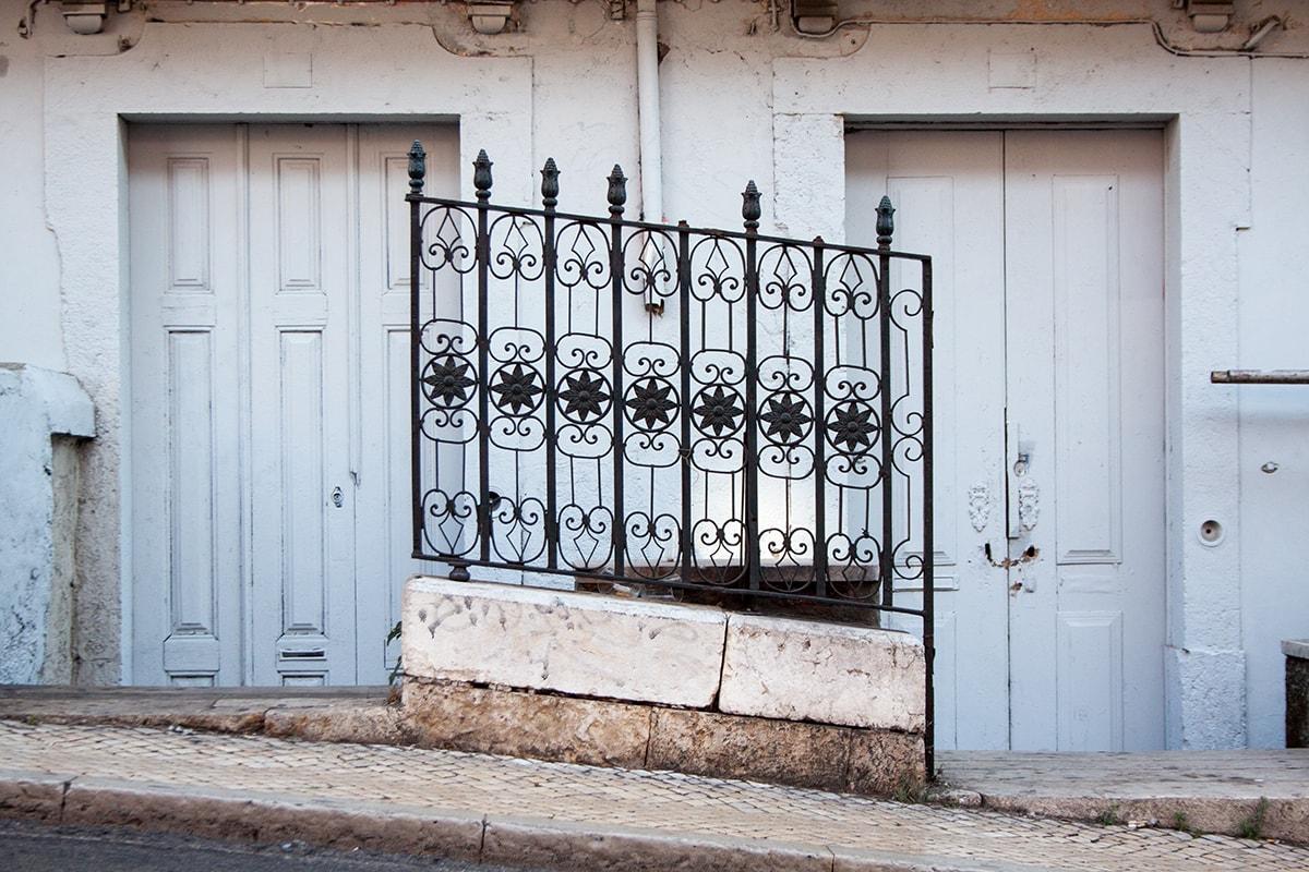 Fotografie. Straßenfotografie. Detaillierter schwarzer Metallzaun vor einer Hausfassade in Lissabon.