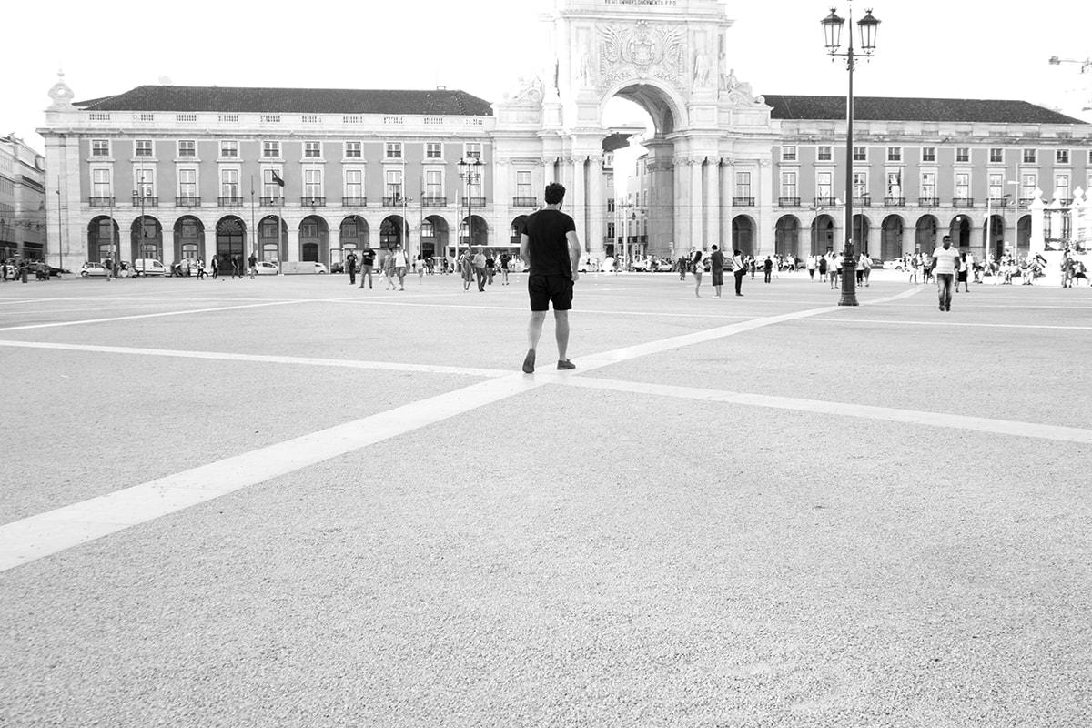 Fotografie. Man läuft auf einer Linie die sich kreuzt. Lissabon.