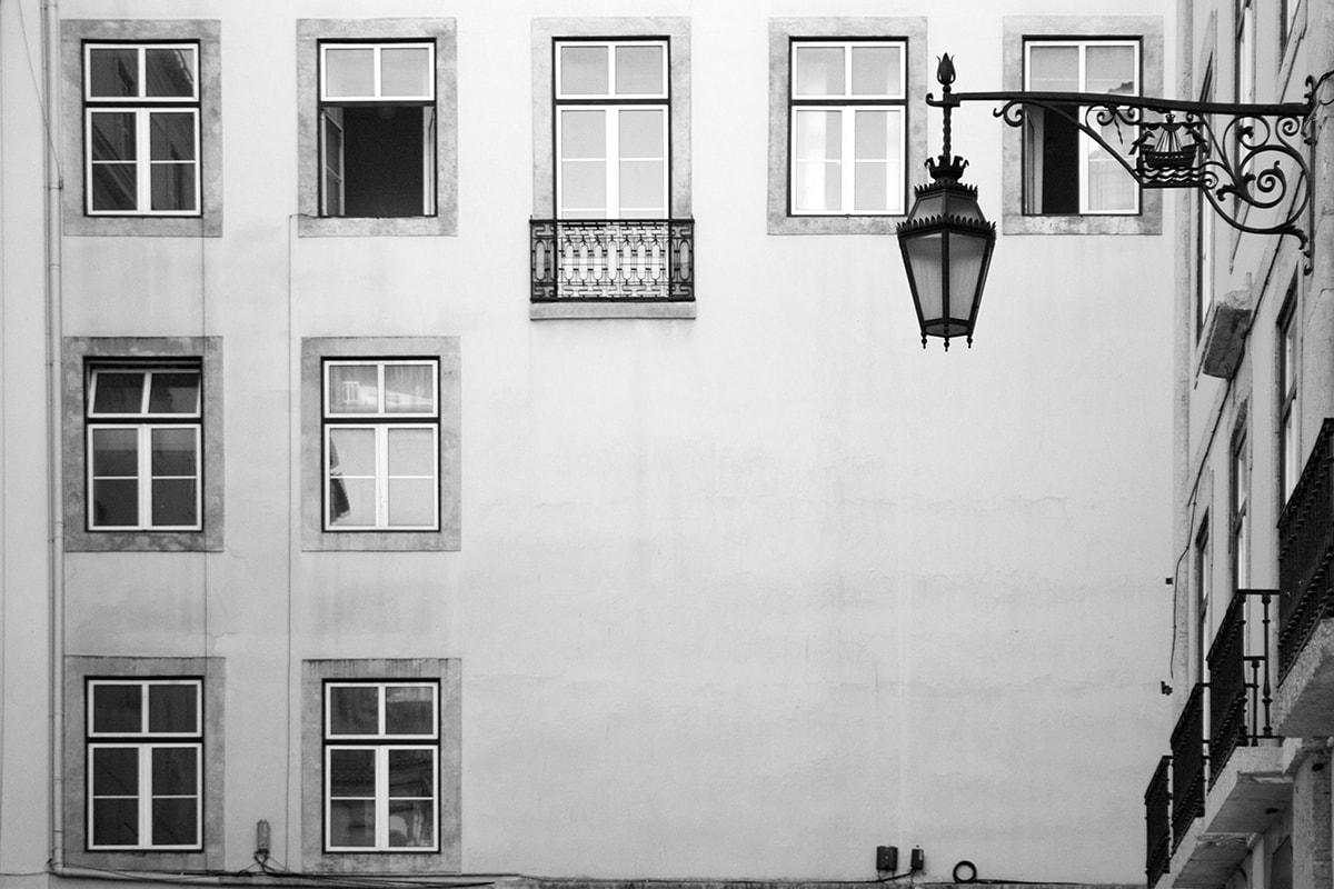 Fotografie. Symmetrische Anordnung von einer Fensterfassade von einem Haus in Lissabon.