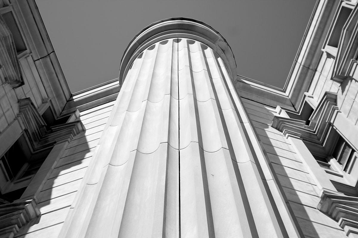 Fotografie. Symmetrische Anordnung. Hausfassade mit Säule aus der Froschperspektive fotografiert.