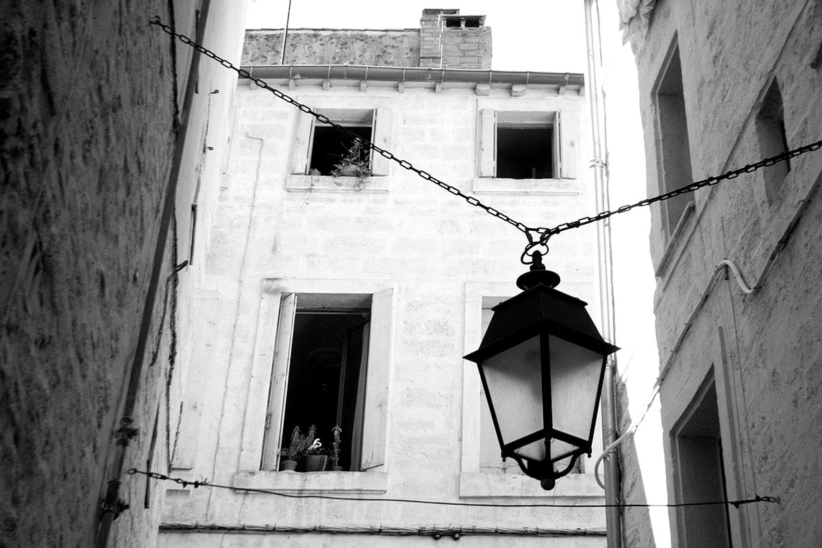 Fotografie. Laternenlampe vor einer steinernen Hausfassade in Montpellier.